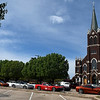 Members of the Enid Corvette Club sit outside St. Francis Catholic Church Wednesday, April 1, 2020. Club members could not attend the funeral of a fellow member's wife due to the covid-19 restrictions but, held a corvette procession to the cemetery. (Billy Hefton / Enid News & Eagle)