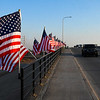 """Traffic passes American flags on Veterans Memorial Bridge (Van Buren overpass) Thursday, April 1, 2021. The flags were posted by the Enid A.M. AMBUCs as part of a """"dry run"""" for it's flag project on the bridge. (Billy Hefton / Enid News & Eagle)"""