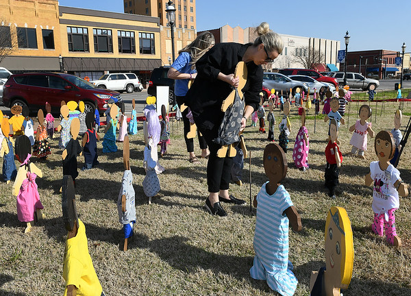 Sarah Herrian places a wooden kid figure on the lawn of the Garfield County Courthouse Thursday, April 1, 2021. The wooden kids respresent the number of child abuse cases in 2020. (Billy Hefton / Enid News & Eagle)