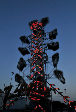 """Baskets on the """"Zipper"""" swing about as it give carnival goers a thrill ride Wednesday at Wagner's Carnival in the Oakwood Mall parking lot. (Staff Photo by BILLY HEFTON)"""