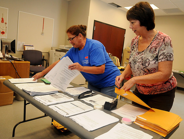 Becky Arens and Susan Purdy (from left), administrative assistants at Longfellow Middle School, assemble information packets for students and teachers Friday, August 9, 2013. Enrollment at the school will be approximately 475, an increase of nearly 50 students since last fall. (Staff Photo by BONNIE VCULEK)