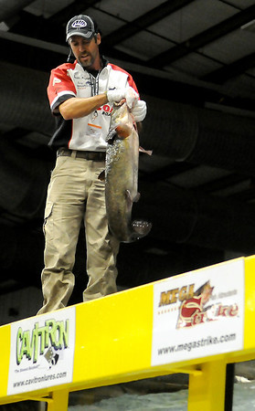 """Jason Reynolds, from Fetch-N-Fish Promotions in Checotah, Okla., holds a giant flathead during a noodling demonstration with Don """"Katt Daddy"""" Brewer, from Mudcats, at the Greater Oklahoma Sportsman's Outdoor Expo at the Chisholm Trail Expo Center Saturday, August 24, 2013. (Staff Photo by BONNIE VCULEK)"""