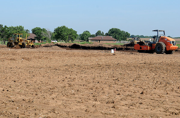 Heavy equipment operators work on the foundation for the new Country Inn & Suites east of Lowes Thursday, August 1, 2013. (Staff Photo by BONNIE VCULEK)
