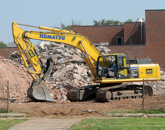 A worker uses a Komatsu excavator to remove debris from the Old Garfield Elementary School location on E. Broadway Tuesday, August 20, 2013. The area will be used as a green space and the new entrance to Longfellow Middle School. (Staff Photo by BONNIE VCULEK)
