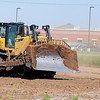 A heavy equipment operator completes dirt work across the street from Prairie View Elementary School Tuesday, August 6, 2013. The City of Enid Street and Maintenance Department is working on a storm detention pond at the location. (Staff Photo by BONNIE VCULEK)
