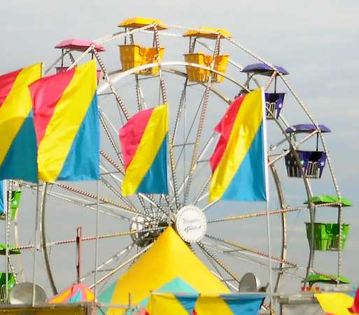 Brilliantly, colored flags wave in the breeze as Wagner Carnival employees set up the ferris wheel at Oakwood Mall Wednesday, August 7, 2013. (Staff Photo by BONNIE VCULEK)