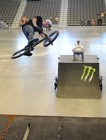 A BMX cyclist gains some air as he readies to perform a trick during the Monster BMX Jam Saturday inside the Enid Event Center. (Staff Photo by BILLY HEFTON)