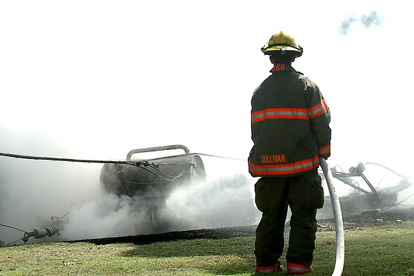An Enid firefighter sprays a transformer that fell from a utility pole Monday in the 900 block of south 2nd street. (Staff Photo by BILLY HEFTON)