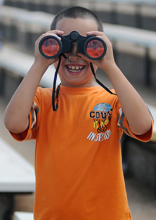 Kobe Brown dons binoculars and grins from ear-to-ear as he watches drivers race at the Enid Speedway Saturday, August 3, 2013. Brown, an avid race car fan, looks forward to the Enid Speedway season-opener next week. (Staff Photo by BONNIE VCULEK)