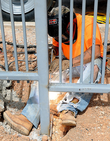 Steven Hollsema, from GMR Construction in Stillwater, welds new fence sections together outside the west entrance to the Enid Event Center. Workers are installing irrigation and lighting systems as they landscape the  area. (Staff Photo by BONNIE VCULEK)