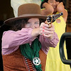 """A young girl covers her ears (back, right) as Sarah Owens fires her six-shooter during the """"Hands-on Circus History"""" at the Cherokee Strip Regional Heritage Center Saturday, August 3, 2013. (Staff Photo by BONNIE VCULEK)"""
