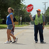 A crossing guard stops traffic at 10th and Chestnut as a parent walks her child home from Coolidge Elementary School Friday, August 23, 2013. Enid Public School students reported to the classroom last Tuesday. (Staff Photo by BONNIE VCULEK)