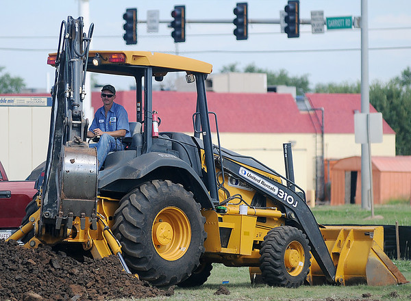 Workers use heavy-equipment as they dig the footing for the new Chick-fil-A near Owen K. Garriott Wednesday, August 7, 2013. Chick-fil-A, owned by Connie Sturgeon-Hart, opened inside Oakwood Mall's food court 29 years ago, but will move to the new location just north of the mall. (Staff Photo by BONNIE VCULEK)