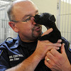Allen Elder, with the Enid Animal Control Center, accepts a kiss from a small puppy Wednesday, August 21, 2013. Elder thanks The Enid SPCA for their recent donation of two Port-a-Cool units to the Enid Animal Control Center. (Staff Photo by BONNIE VCULEK)