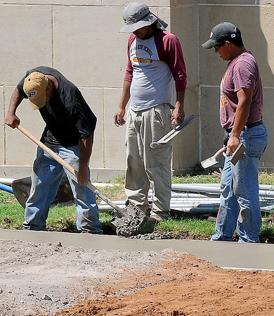 A worker fills in the edge of a new concrete sidewalk as men smooth the area on the northeast corner of the Garfield County Court House Tuesday, August 27, 2013. (Staff Photo by BONNIE VCULEK)