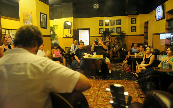Guests listen as Billy Beck plays the guitar in the Broadway Cafe & Lounge during First Friday, August 2, 2013. (Staff Photo by BONNIE VCULEK)