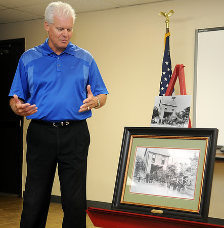 Steve Kime glances toward a pencil drawing of the Enid Firehouse 1906 rendered by artist, Duron Lewis, during a special reception at the Enid Fire Department Central Station Thursday, August 22, 2013. Lewis presented the art to City of Enid officials, Enid Fire Chief Joe Jackson and the Enid Fire Department in appreciation for their efforts as first responders. (Staff Photo by BONNIE VCULEK)