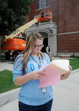 Scout McGinnis, a junior at Enid High School, reviews her fall schedule as she waits for a ride Thursday, August 8, 2013. Approximately 1900 high school students will begin classes on August 20. (Staff Photo by BONNIE VCULEK)