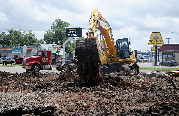 Jackson's Wrecking and Demolition remove the One Hour MOTO PHOTO foundation at 220 S. Van Buren Friday, August 9, 2013. MOTO PHOTO Portraits & Digital Imaging Lab moved to 2213 W. Willow in Willow Plaza last November. (Staff Photo by BONNIE VCULEK)