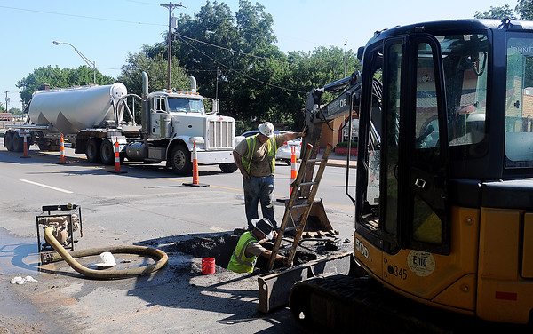 As traffic moves through a work zone, City of Enid Street and Traffic Public Service Division employees, Jeremy Meier (top, center) and Michael Humphries (bottom, center) repair a broken water line on S. Van Buren, between York and Indian. (Staff Photo by BONNIE VCULEK)