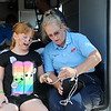 Maecee Emmerson (left) has her oxygen level taken by Barbara Friend, from Life EMS, as children and their parents inspect the inside of an ambulance at the Leonardo's Discovery Warehouse Enid Mack Truck Motor Mania Saturday, August 24, 2013. (Staff Photo by BONNIE VCULEK)