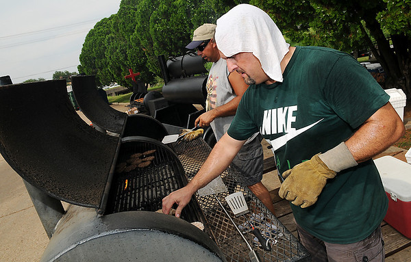 Tommy Lawson and Scott Messenger grill hamburgers during the Feed the Neighborhood event Sunday at Government Springs Park. (Staff Photo by BILLY HEFTON)