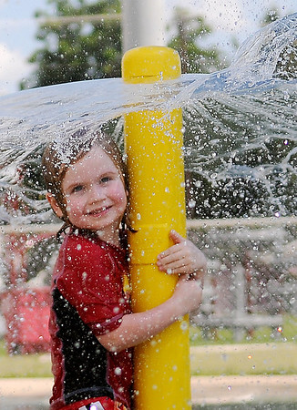 Aedan Dowell, son of Evi Dowell, reacts as a breeze blows refreshing water onto his face at Champion Splash Pad. Dowell frolicked in the water alone until Enid area school's dismissed for the weekend. (Staff Photo by BONNIE VCULEK)