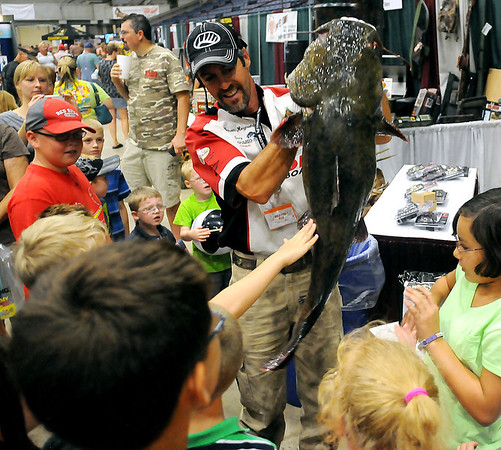 """Jason Reynolds, with Fetch-N-Fish Promotions from Checotah, Okla., holds a giant flathead catfish for children to touch during the Greater Oklahoma Sportsman's Outdoor Expo at the Chisholm Trail Expo Center Saturday, August 24, 2013. Don """"Katt Daddy"""" Brewer demonstrated the art of noodling for large crowds during the event. (Staff Photo by BONNIE VCULEK)"""