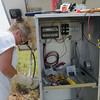 Amie Gibson, from the Oklahoma Geological Survey Observatory in Leonard, installs a new seismology station near Carrier Friday, August 2, 2013. (Staff Photo by BONNIE VCULEK)