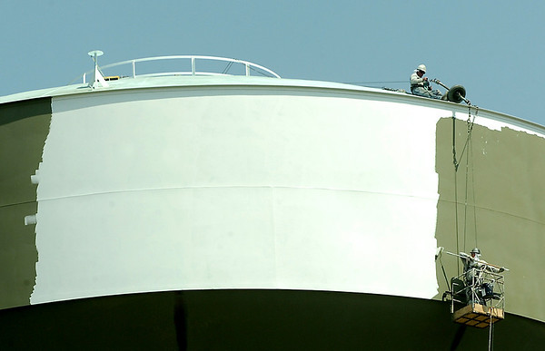 Painters work on painting the new water tower on east Chestnut Tuesday. (Staff Photo by BILLY HEFTON)