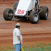 A race car speeds through turn three above a racing official at the Enid Speedway Saturday, August 3, 2013. Thirty-seven drivers competed in the unofficial play day before the season-opener next weekend. (Staff Photo by BONNIE VCULEK)