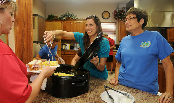Raegan Guffy (center) and her mother-in-law, Becky Guffy (right), serve fresh Ringwood Gold corn-on-the-cob to a guest at the Oklahoma Hearts for Adoption luncheon at the First Baptist Church during Ringwood Watermelon Fest Saturday, August 31, 2013. All proceeds provide financial assistance to adoptive parents and advocates for the fatherless. (Staff Photo by BONNIE VCULEK)
