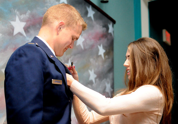 2nd Lt. Garen Jeppesen gets his wings pinned on by his wife during graduation ceremonies for the Joint Specialized Undergraduate Pilot Training Class 13-13 Friday at vance Air Force Base. (Staff Photo by BILLY HEFTON)