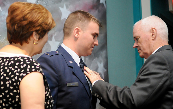 2nd Lt. Jonathan Payne gets his wings pinned on by his parents during graduation ceremonies for the Joint Specialized Undergraduate Pilot Training Class 13-13 Friday at vance Air Force Base. (Staff Photo by BILLY HEFTON)
