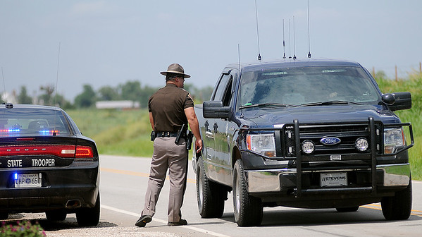 The Oklahoma Highway Patrol and Garfield County Sheriff Department investigate an accident near the intersection of OK 132 and W. Purdue after  the driver of a Chevrolet Camaro avoided another car in her lane and hit a highline pole Wednesday, August 7, 2013. O.G.&E. service line crews were called to replace downed power lines near the entrance to Brainard Dairy, 3 miles north of U.S. 412 on OK 132. (Staff Photo by BONNIE VCULEK)
