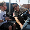 Bob Bennett, a volunteer deputy with the Garfield County Sheriff Department, shows Riley Smith how to turn on the lights of the department's 4-wheeler during the Enid Mack Truck Motor Mania at Leonardo's Discovery Warehouse Saturday, August 24, 2013. (Staff Photo by BONNIE VCULEK)