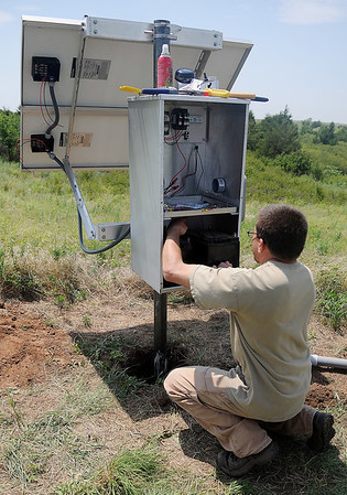 Austin Holland with Oklahoma Geological Survey installs a new seismology station near Carrier Friday, August 2, 2013. (Staff Photo by BONNIE VCULEK)