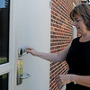 Heather Reames, science instructor at Emerson Middle School, uses her identification card to enter the building at 700 W. Elm Tuesday, August 27, 2013. During the recent school bond remodel all exterior doors were replaced as part of the new school safety procedures. (Staff Photo by BONNIE VCULEK)