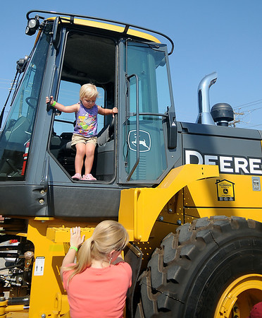 Little Abigail Starr looks for an easy way off a John Deere 644K Loader during Leonardo's Discovery Warehouse Enid Mack Truck Motor Mania Saturday, August 24, 2013. (Staff Photo by BONNIE VCULEK)