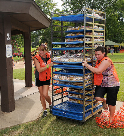 Tina Dutcher and Lori Peterson move a rack of buns into place as they prepare for the Feed the Neighborhood event Sunday at Government Springs Park. (Staff Photo by BILLY HEFTON)