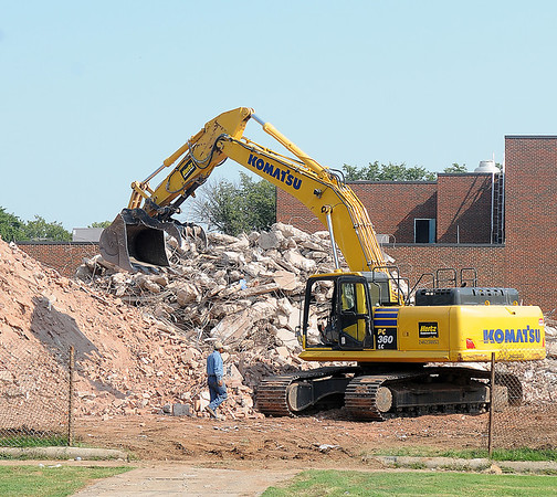A heavy equipment operator returns to his Komatsu excavator as he assists with debris removal from the old Garfield Elementary School Tuesday, August 20, 2013. (Staff Photo by BONNIE VCULEK)