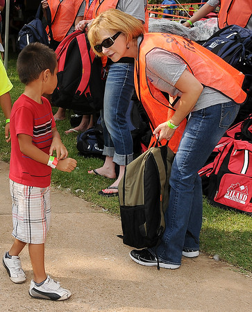 Volunteer, Vanessa Gainer, hands out backpacks during the Feed the Neighborhood event Sunday at Government Springs Park. (Staff Photo by BILLY HEFTON)