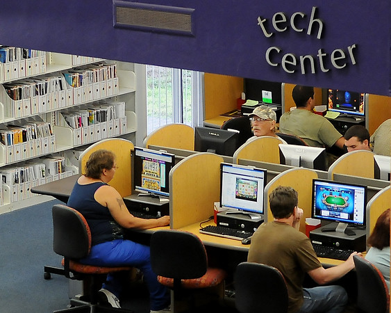 Visitors to the Public Library of Enid and Garfield County take advantage to the tech center Monday. The library will close for ten days later this month for cleaning and maintenance. (Staff Photo by BILLY HEFTON)
