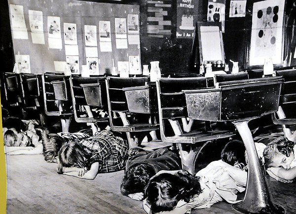 Children duck and cover during an atomic bomb drill at their elementary school. (Staff Photo by BONNIE VCULEK)