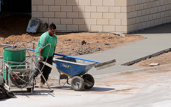 A worker finishes the brooming of a new concrete sidewalk section at the Garfield County Court House Tuesday, August 27, 2013. (Staff Photo by BONNIE VCULEK)