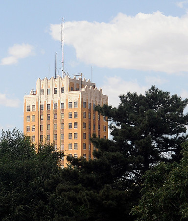 Several floors of the Broadway Tower appear above a tree line near downtown Enid Friday, August 30, 2013. (Staff Photo by BONNIE VCULEK)