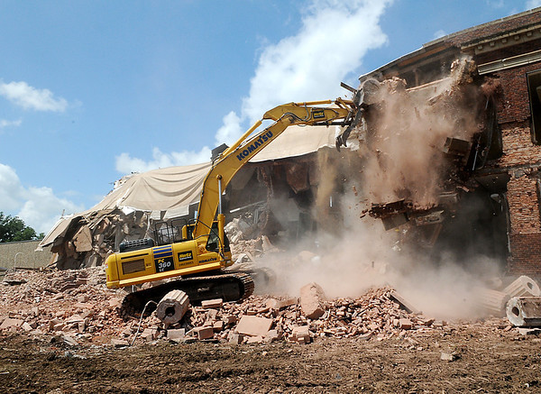 A chunk of the old Garfield Elementary falls as a track hoe demolishes the school Tuesday. (Staff Photo by BILLY HEFTON)
