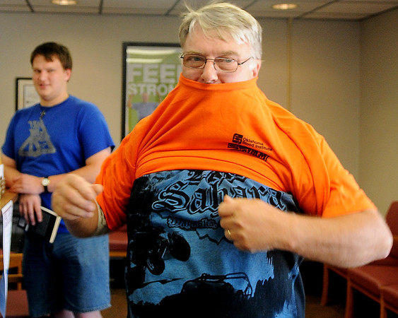 Rodney Batchelder tries on his new OSU t-shirt after donating blood at the Northwest Oklahoma Blood Institute Friday, August 30, 2013. More than 70 registered during the first day of the OU-OSU Bedlam Blood Drive. Those who give blood are entered into a drawing for two tickets to the OU-OSU Bedlam football game in Stillwater on December 7. (Staff Photo by BONNIE VCULEK)