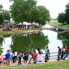 Attendees encircle the pond at Government Springs Park during the Feed the Neighborhood event Sunday. (Staff Photo by BILLY HEFTON)