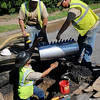 Michael Humphries (bottom, left) reaches for a large clamp as City of Enid Street and Traffic Public Service Division employees repair a water line on Van Buren between York and Indian Tuesday, August 27, 2013. (Staff Photo by BONNIE VCULEK)